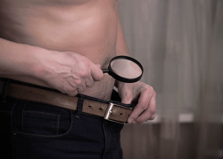 impotence: Guy having size worries and checking out with a magnifying glass. Health and impotence