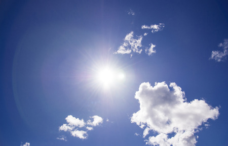The sun shines bright in the daytime in summer. Blue sky and clouds.