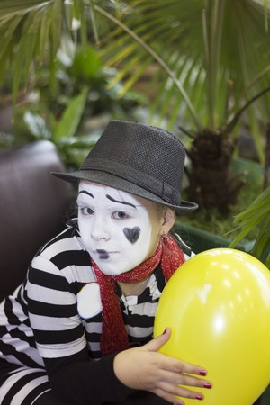Girl with a yellow balloon in the form of mime actor Stock Photo