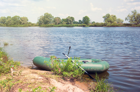 Inflatable boat on the a river near shore.