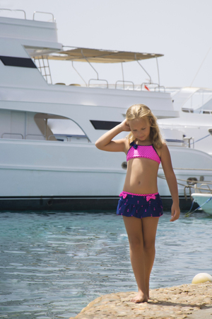 Beautiful girl strolls along the shore of the stone on the background of yachts.