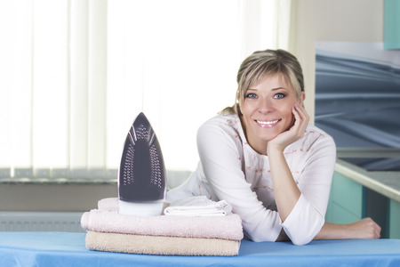 Beautiful young woman is leaning on ironing board, looking at camera and smiling while ironing clothes at home. Stock Photo