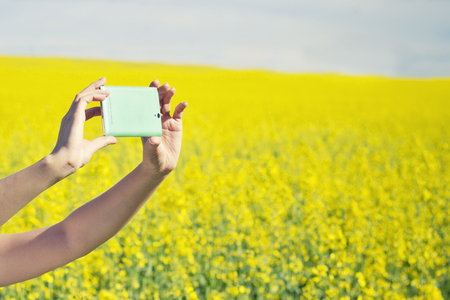 Technology, summer holidays, vacation and people concept - hands of woman taking photo or selfie by smartphone on rape field