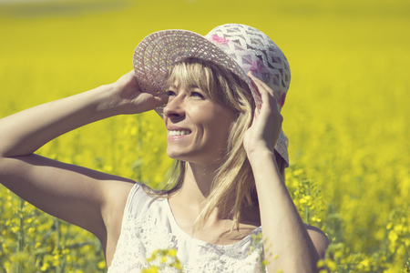 Young woman with a hat enjoying summer on the rape field. Stock Photo