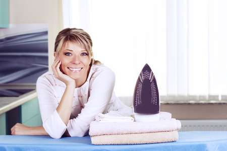 Beautiful young woman is leaning on ironing board, looking at camera and smiling while ironing clothes at home