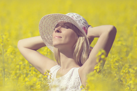 Young woman with a hat enjoying summer on the rape field Stock Photo