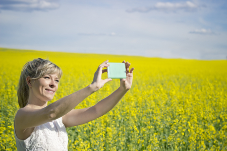 canola: Technology, summer holidays, vacation and people concept - hands of womantaking selfie by smartphone on rape field