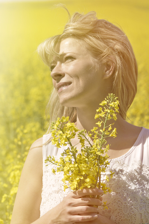 Beautiful dreamy woman in a rapeseed field with a bouquet dreams and enjoys nature