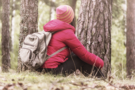 Woman tourism. Back of traveler in the forest looks for the road. Beautiful young woman is traveling and resting in the forest. 版權商用圖片