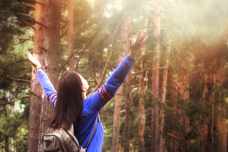 Hiker woman with raised arms up on nature outdoors, back view Stock Photo