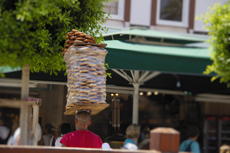 Street vendor carries stack of bagels (simit) on his head. Simit is traditional turkish berakfast snack, very popular in Turkey