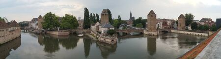 Medieval bridge Ponts Couverts with towers, view from the Barrage Vauban, landmark 17th-century fortification, on a cloudy day, Strasbourg, France - June 12, 2015