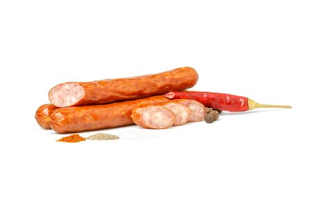 Three beer sausages, sliced sausage slices, a handful of ground red pepper, hot black pepper, allspice fruit, chili pepper in a pod and a handful of salt isolated on a white background. Standard-Bild