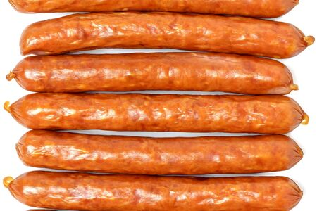 Background of dry sausages. Kabanos sausages folded in a row close-up on a white background.