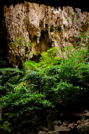 caving: Beautiful stone Cave with above light in Thailand. Stock Photo