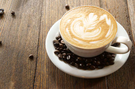 closeup view of a cup of coffee and coffee beans on wooden table        Stock Photo