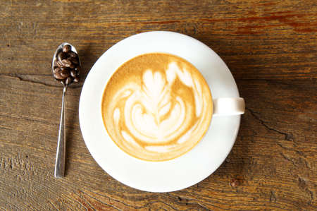 cup of latte art and coffee beans in spoon on wooden table