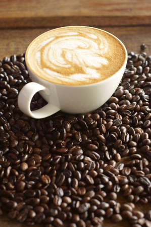 Coffee cup with coffee beans background Stock Photo