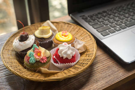 Laptop and cupcakes on wood table.