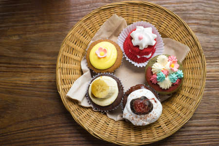 Mixed cupcakes on wood table. Stock Photo