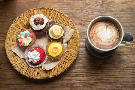 Cupcakes with hot chocolate on old wooden table.