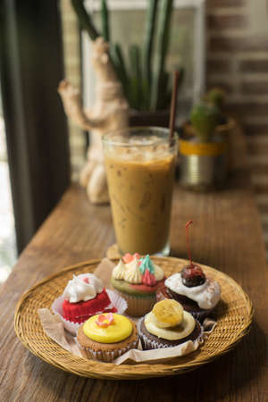Cupcakes with iced latte on old wooden table.