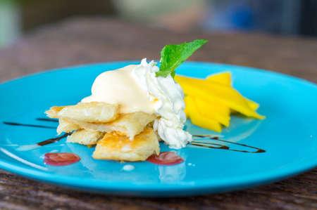 Pancake with mango on table wood