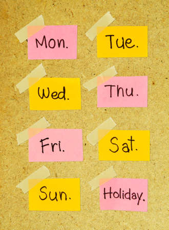 Days of the week note with masking tape on wood background.