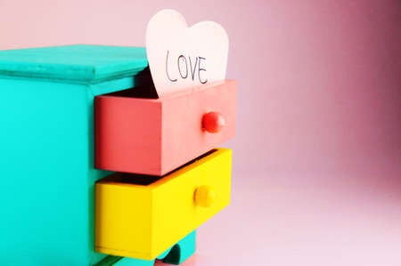 Wording, Love. On pink heart paper note in drawer vintage wood box.