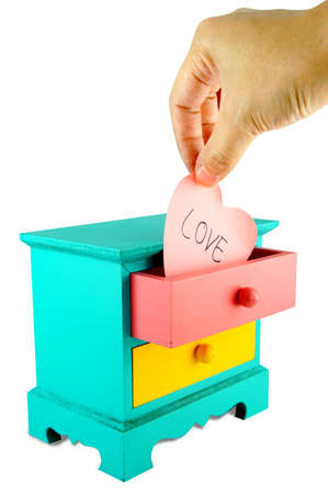 Wording, Love. On pink heart paper note in drawer vintage wood box on white background.