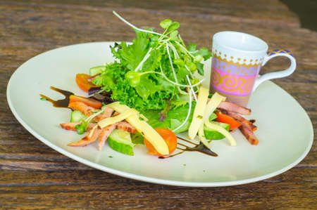 Salad with greens on wooden table