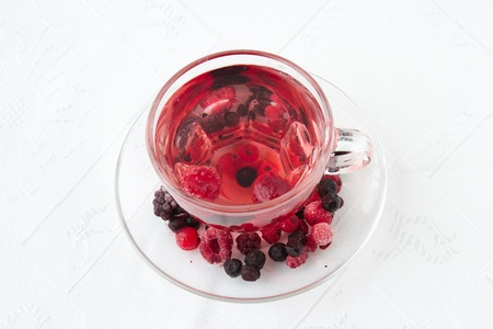 Red drink from mixed berries in trasparent cup decorated with frozen berries  Stock Photo