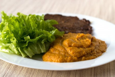 Chestnut-carrot-pumpkin mashed mix with green salad and a beef steak on the white plate
