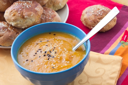 Pumpkin mashed soup with white and black sesame, handmade sesame buns on the background