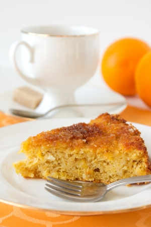 Orange pie on white plate with a cup of tea and oranges