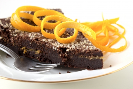 Chocolate cake with orange layer on white plate decorated with orange zest