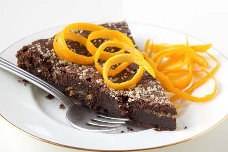 Chocolate cake with orange layer on white plate decorated with orange zest  photo