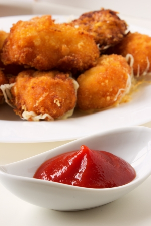 Ketchup with nuggets on the background on white plate  Selective focus  photo
