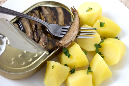 Canned sprats in oil with potatoes on white plate