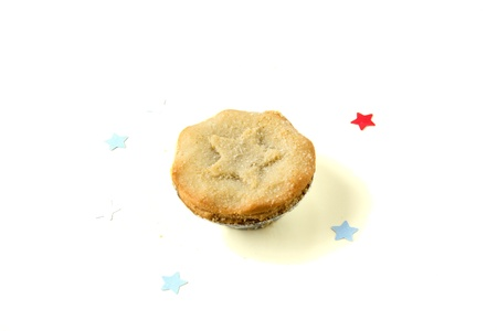 Christmas mincemeat pie decorated with a star. Small start are around.