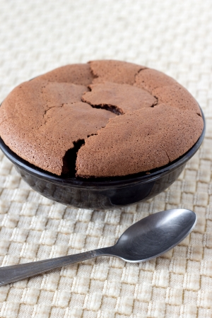 Chocolate souffle in earthenware brown dish with a spoon