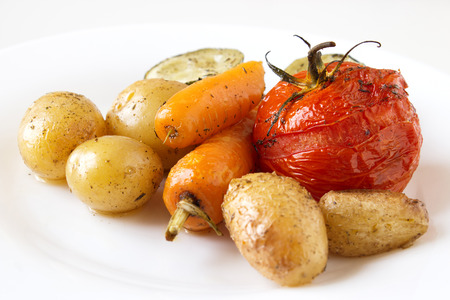Baked potatoes, tomatoes, carrots and zucchini on white background.