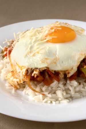 Basque egg with rise on white plate. Hot basque traditional food with pepper. Stock Photo