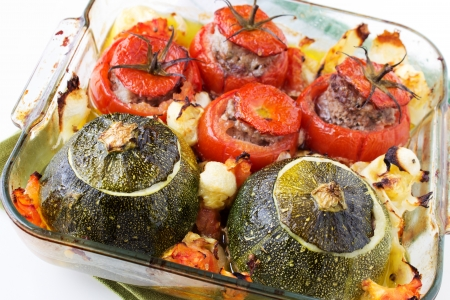 Transparent plate with cooked tomatoes and marrows stuffed with minced meat with sauce. Stock Photo - 23043073