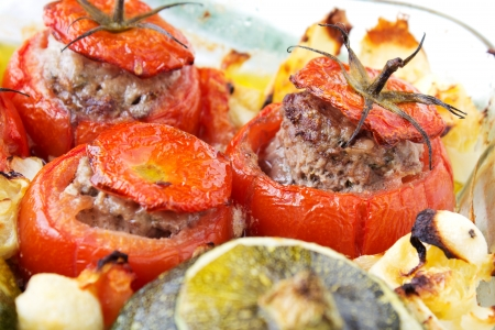 Transparent plate with cooked tomatoes and marrows stuffed with minced meat with sauce. Stock Photo