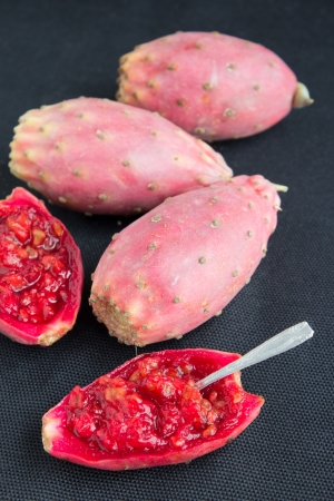 Red cutted prickly pear (also called devils fig) on the black background. Stock Photo