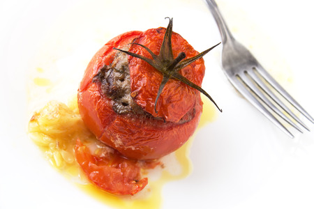 White plate with cooked tomatoe stuffed with minced meat with sauce. Fork and knife on the background.