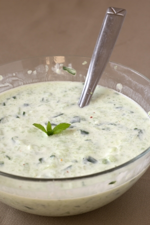 Tzatziki in glass bowl on brown background.