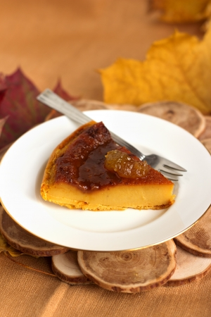 Pumpkin pie with caramel decorated with jam on white plate in natural wood background