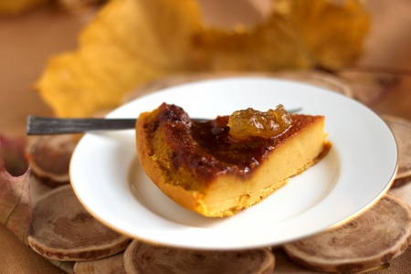 Pumpkin pie with caramel decorated with jam on white plate in natural wood background  Selective focus  Stock Photo